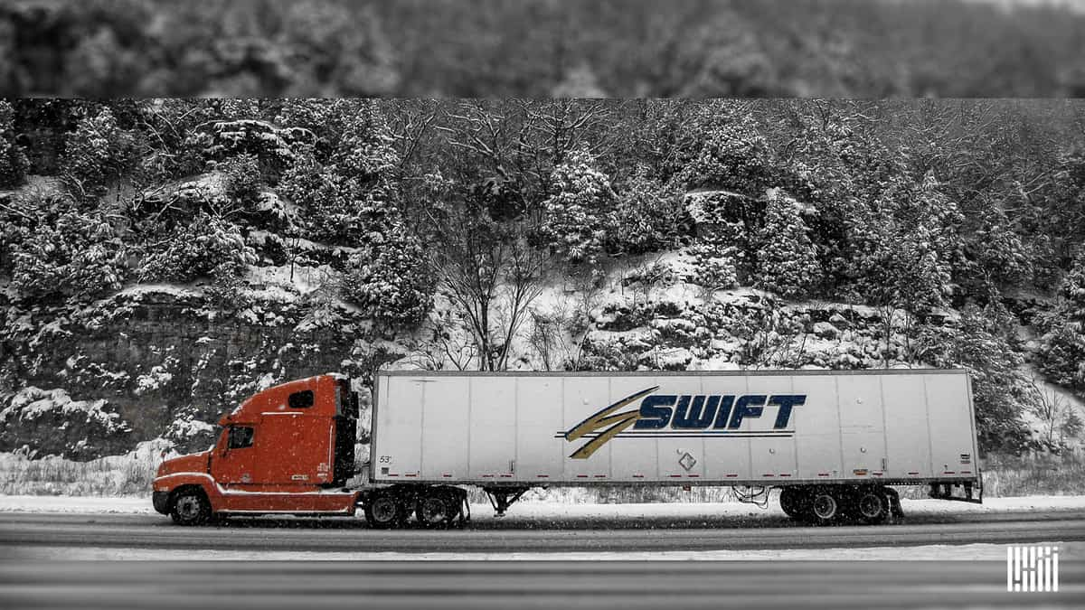 Tractor-trailer heading down snow road with snowy hillside in background.
