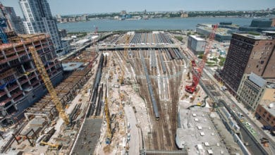 A photograph of a rail yard in construction. The yard is in a city next to a river.