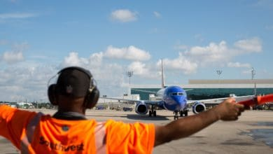 Southwest ground worker directs a plane where to go.