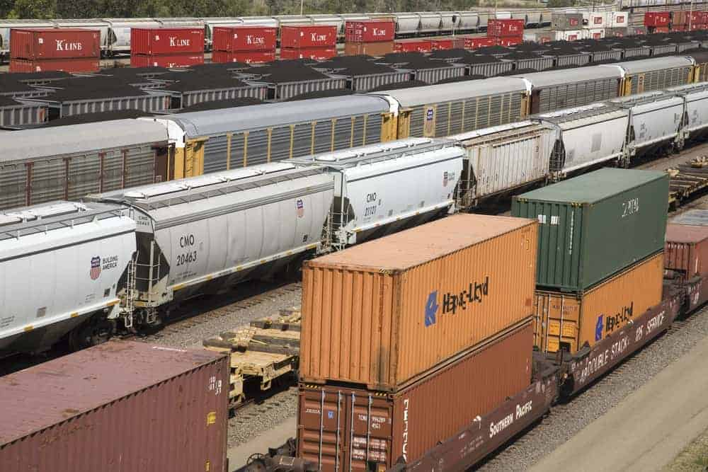 A photograph of different types of railcars sitting on rail tracks at a rail yard.