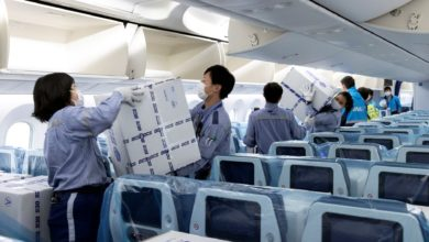 Workers put boxes in airline seats.