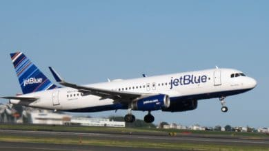 A blue and white JetBlue plane takes off.