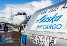 An Alaska Airlines shipping container sits on tarmac in front of plane.