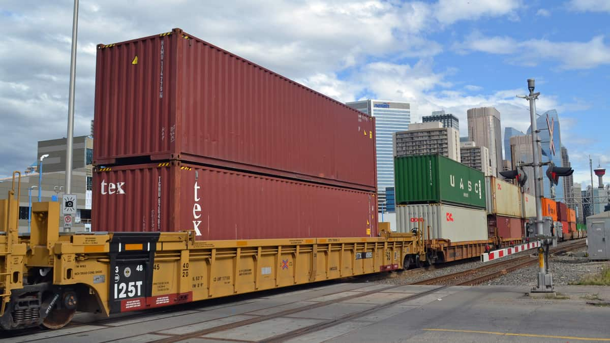 A photograph a train carrying intermodal containers. Tall city buildings are in the background.