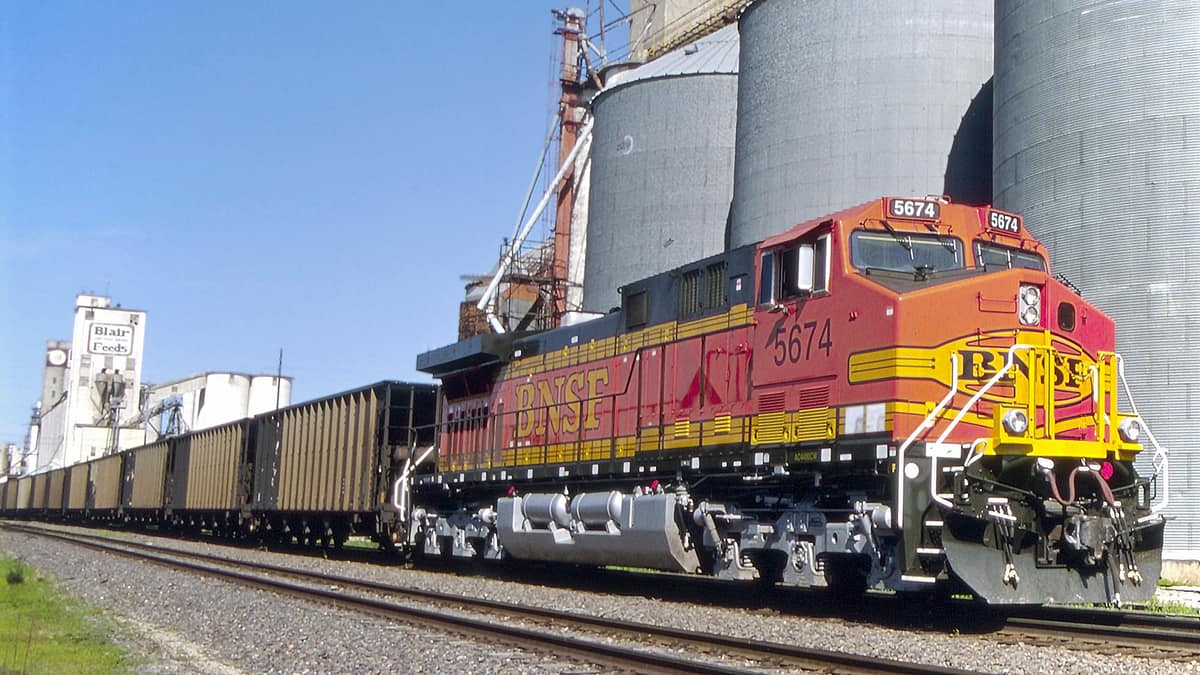 A photograph of a train in front of silos.
