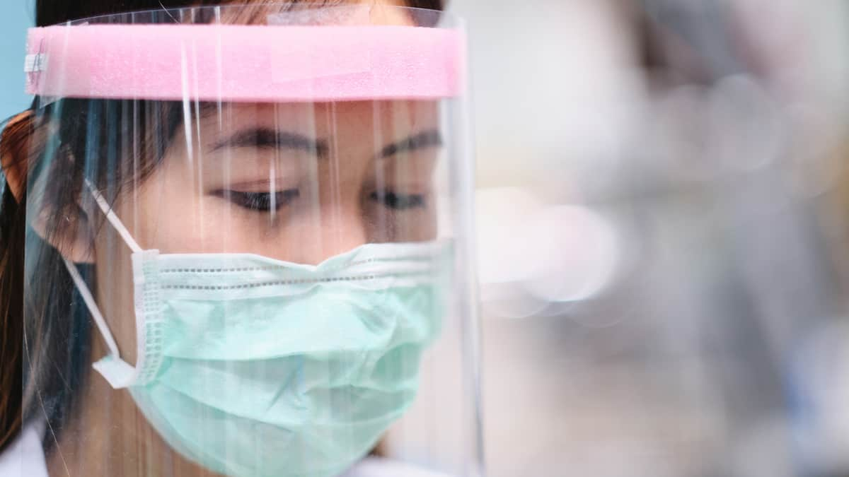 Healthcare worker wearing protective mask and face shield.