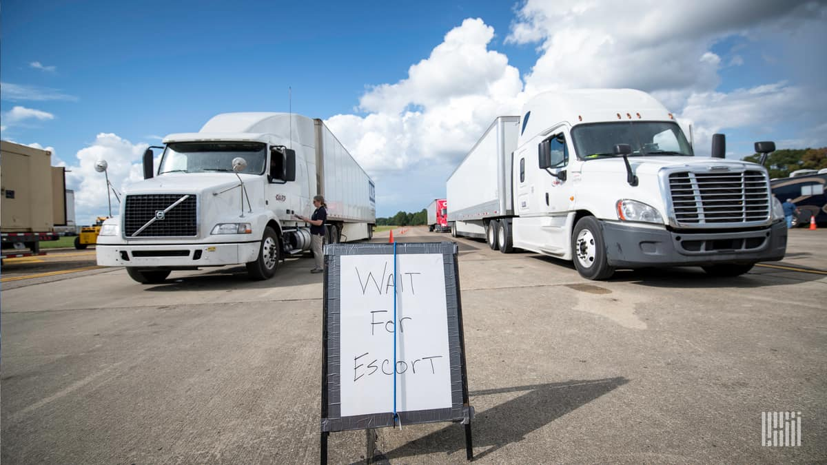 "Trucks lined up ready to deliver supplies. Sign says: ""Wait for Escort."""