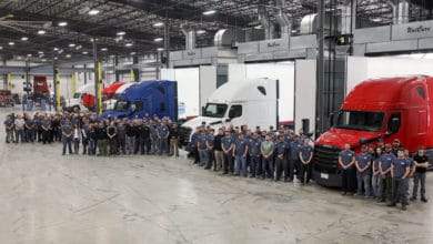 Group of truck repair workers gathered in front of red, blue and white trucks
