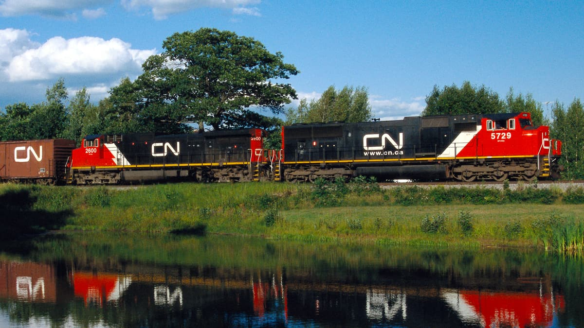 A photograph of a train. It is running next to a pond and a reflection of the train is on the pond's surface.