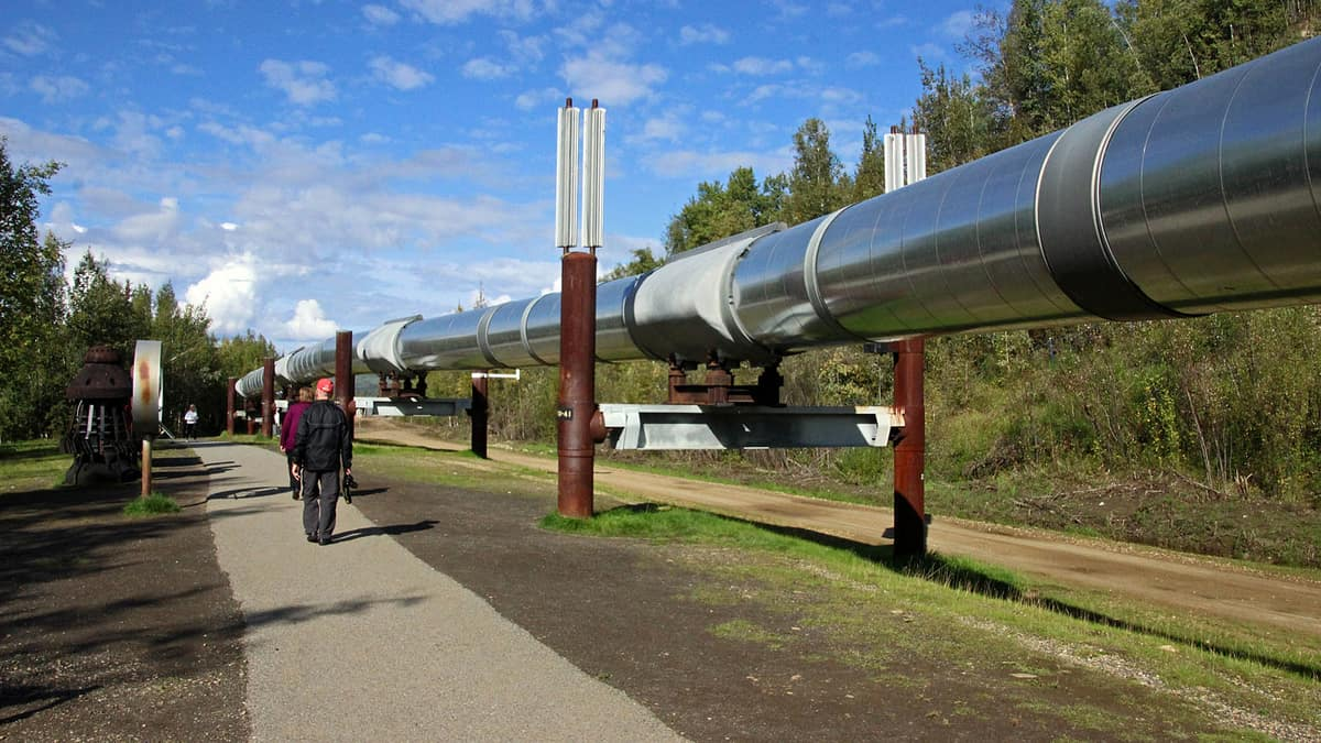 Part of the Trans-Alaska pipeline system (above-ground) with workers walking by it.