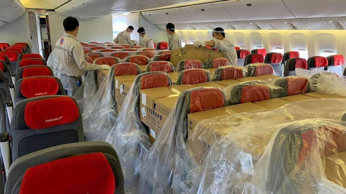 Austrian Airlines cargo handlers loading freight in the seats of a passenger airplane.