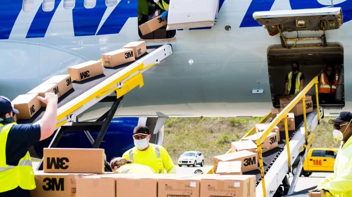 Ground workers unload boxes through aircraft doors.