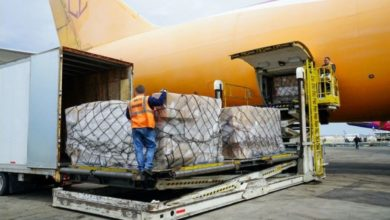 A yellow cargo plane is unloaded.