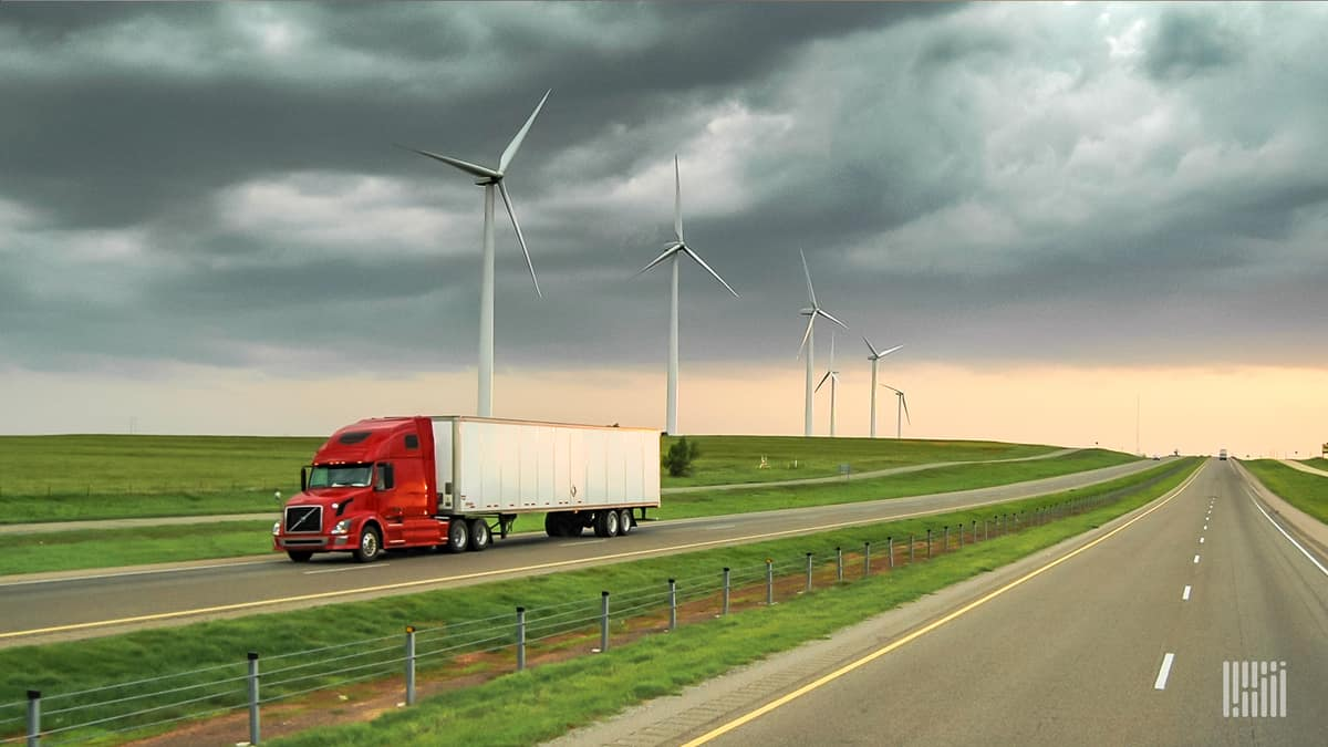 Truck driving on highway with wind turbines