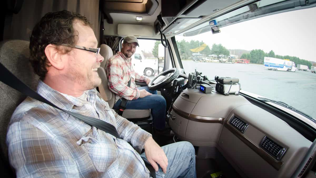 Two truck drivers smiling at each other.