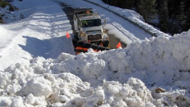 Plow clearing very snowy Idaho highway.