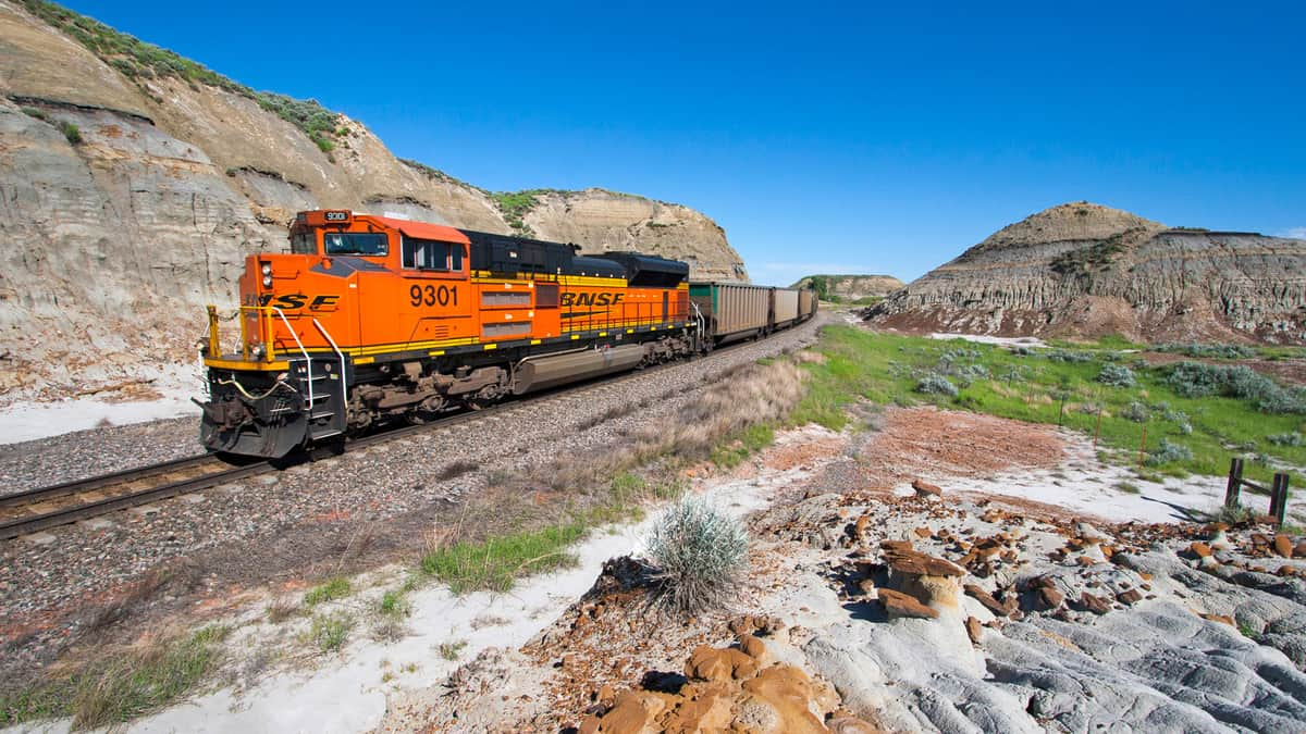 Two BNSF locomotives pull a freight train through the American West.
