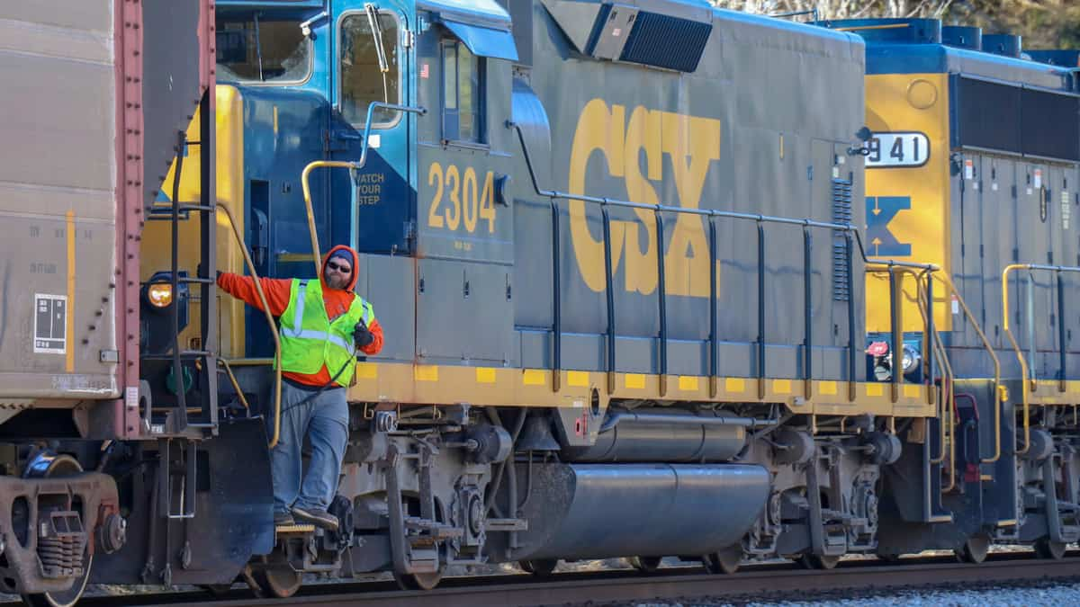 A CSX employee stands on the stairs of a CSX locomotive.