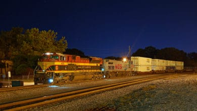 A photograph of a train taken at night.