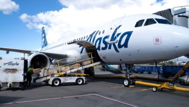A white Alaska Air plane gets loaded through lower deck.