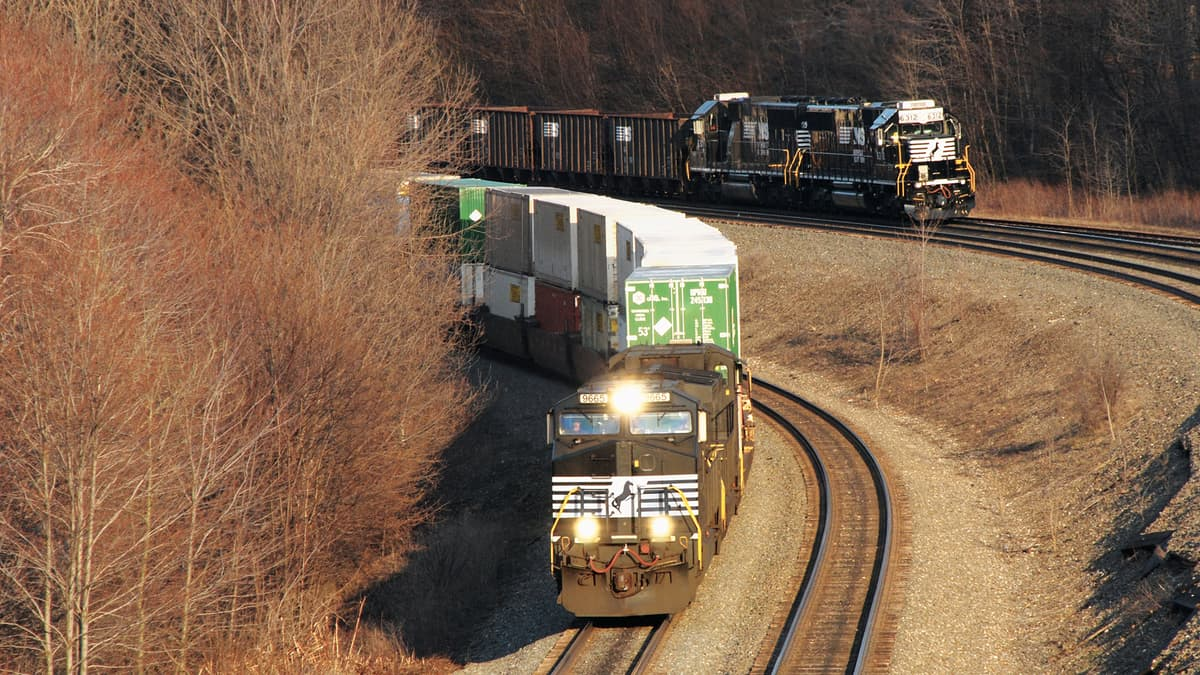 A photograph of two trains pulling intermodal containers and railcars.