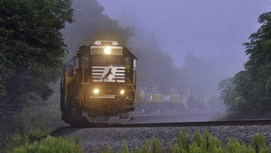 A photograph of a locomotive engine hauling railcars through the fog.