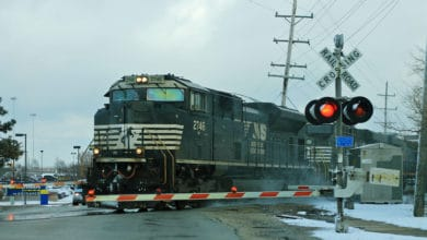 A photograph of a train at a railroad crossing.