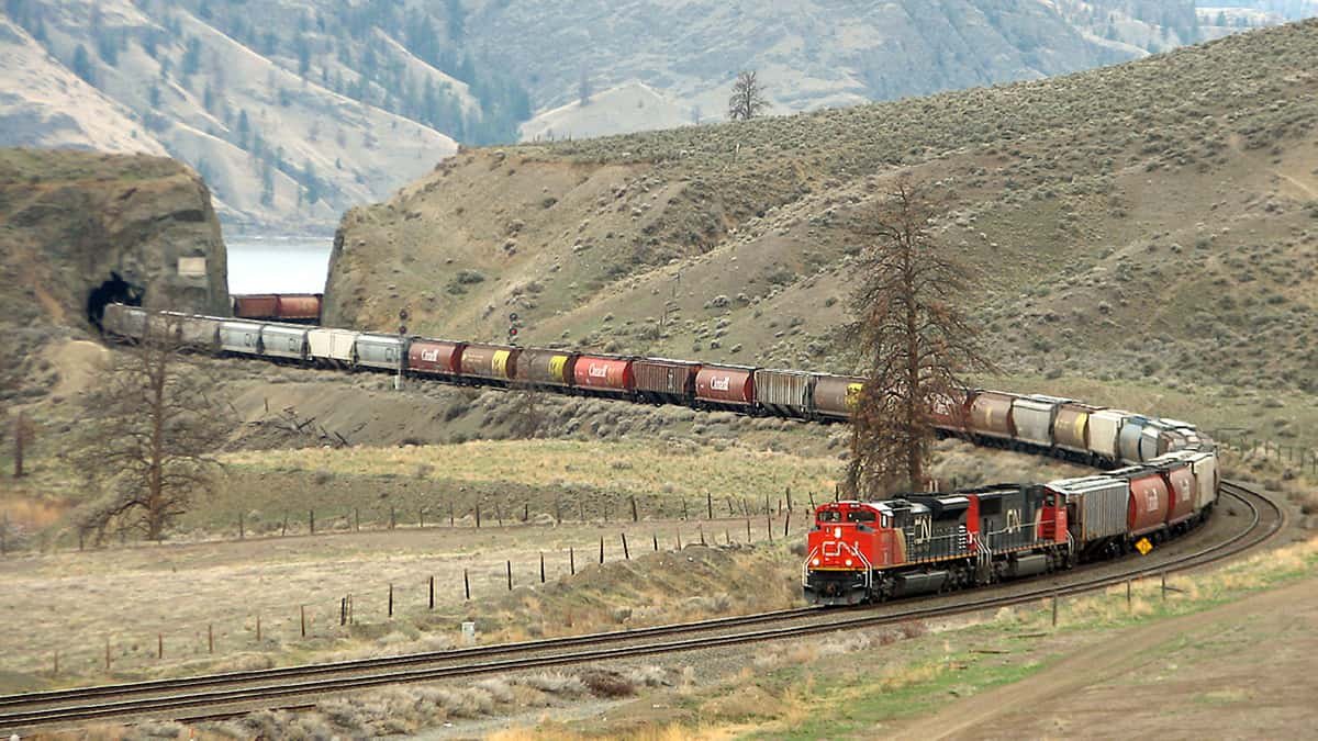 A photograph of a train hauling dozens of railcars behind it.