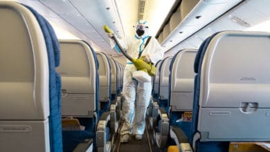 A cabin gets sprayed with disinfectant by someone in a hazmat suit