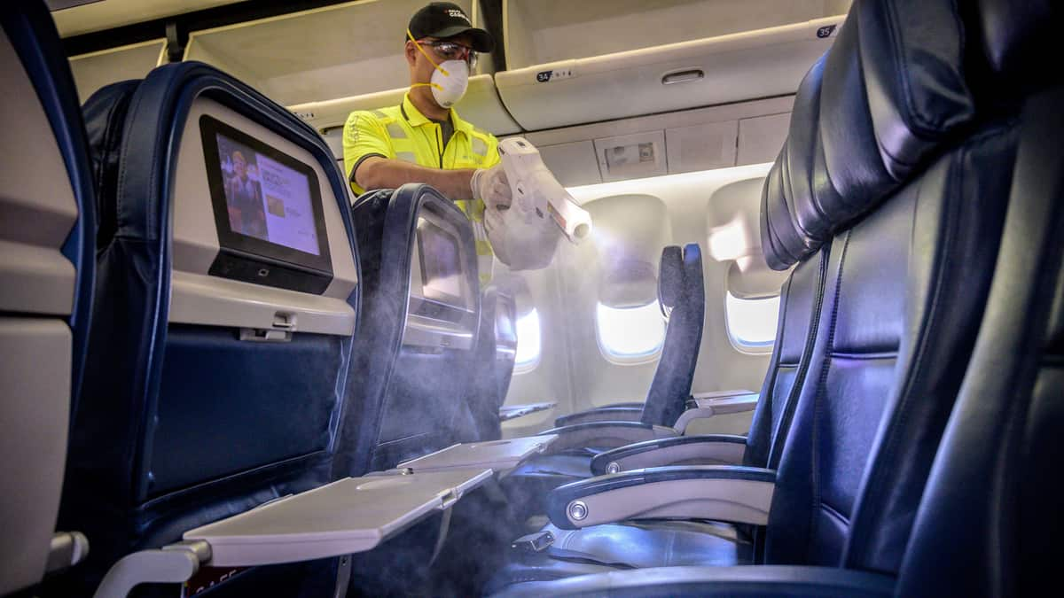 A maintenance worker sprays an airplane cabin to disinfect it.