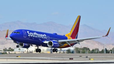A bright blue and orange Southwest plane landing.