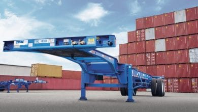 A photograph of a chassis. There are intermodal containers in the background.