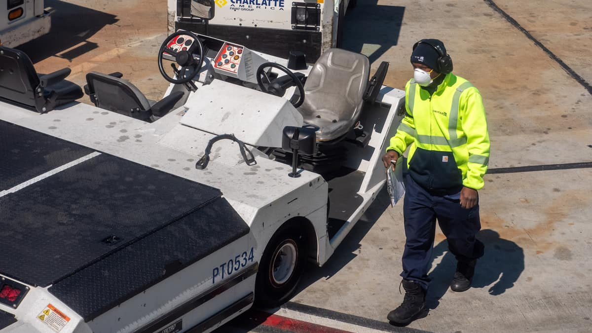 Baggage handler on tarmac with face mask.