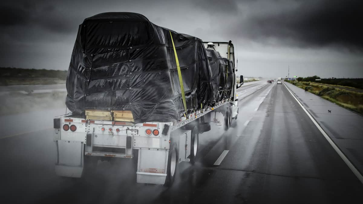 Covered flatbed tractor-trailer on wet highway.