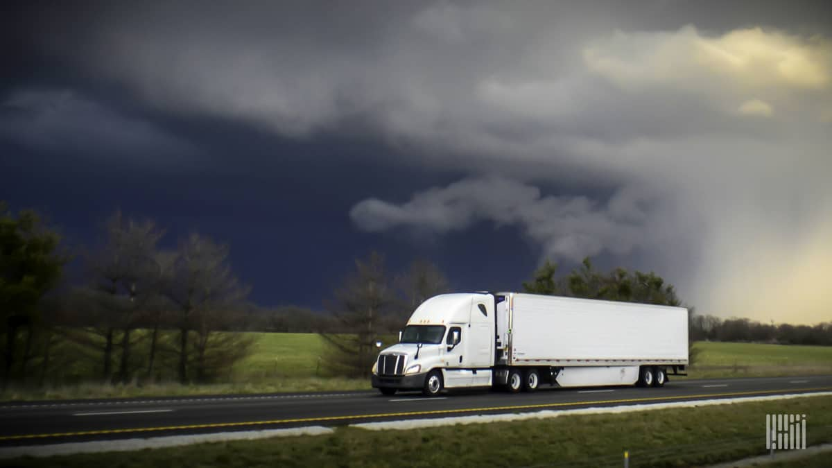 Tractor-trailer heading down highway with thunderstorm cloud in background.