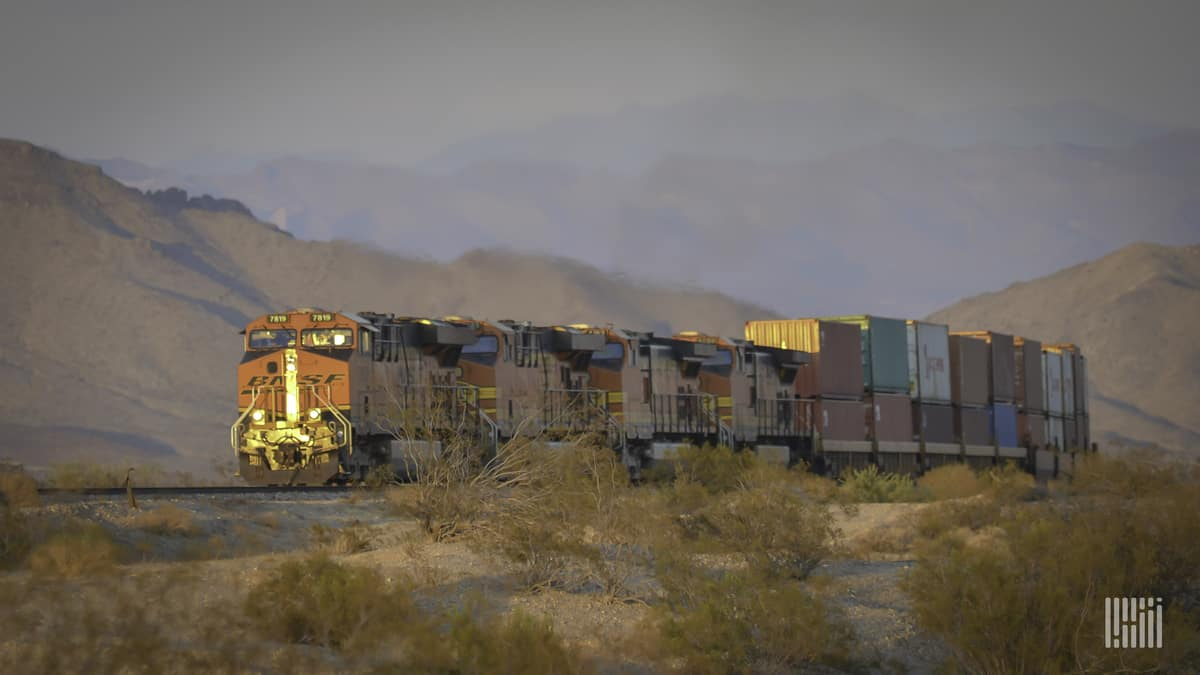 A train hauling railcars through a field. There is a mountain range in the background.