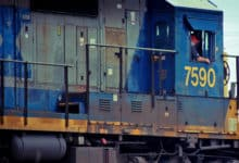 A photograph of a man inside a locomotive engine. He is by the window.