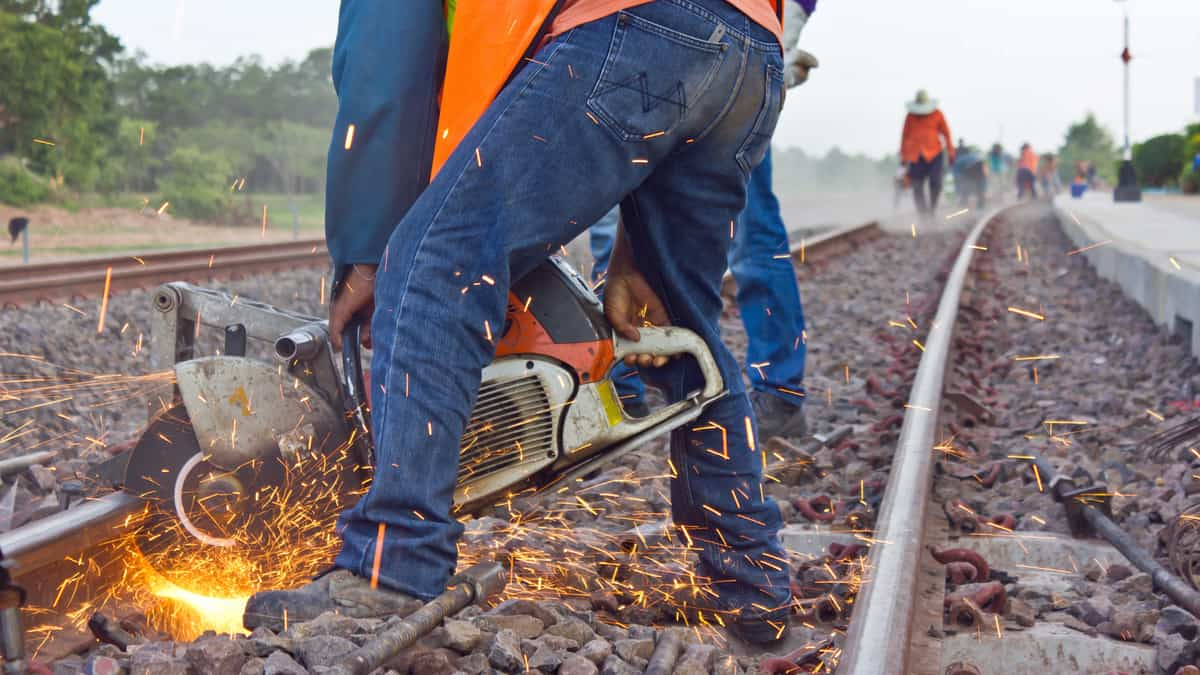 A photograph of a worker fixing some rail track.