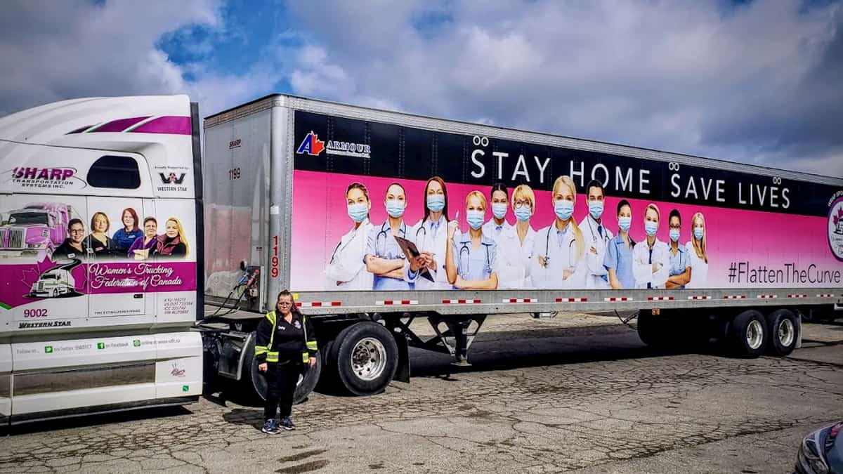 "Shelley Uvanile-Hesch standing in front of her tractor-trailer, wrapped with the message ""Stay Home. Save Lives"""