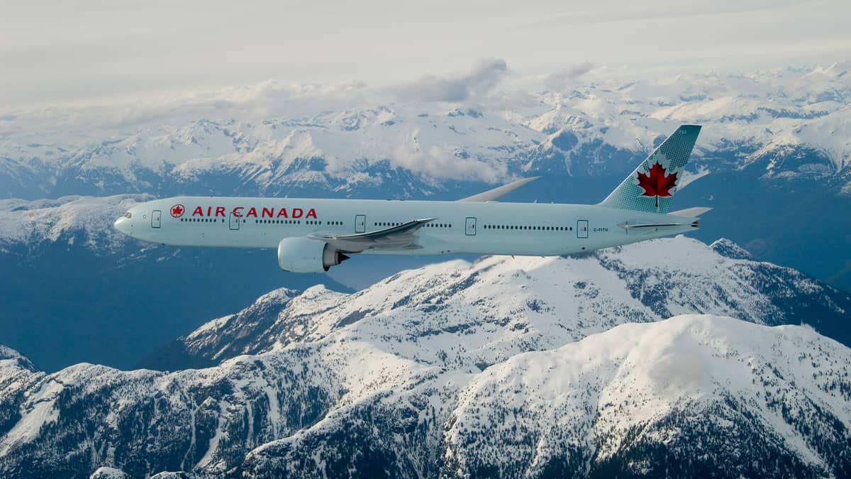 Big white plane flies high over snow-capped mountains.