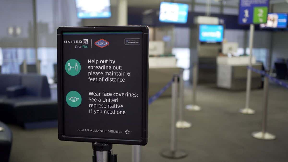 A sign at the ticket counter tells travelers to space out so they don't spread germs.
