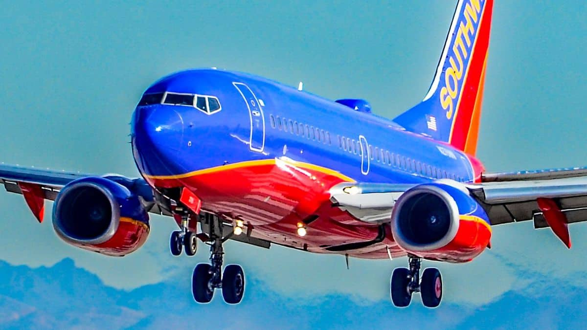 Bright blue and orange Southwest jet comes in for landing wheels down.