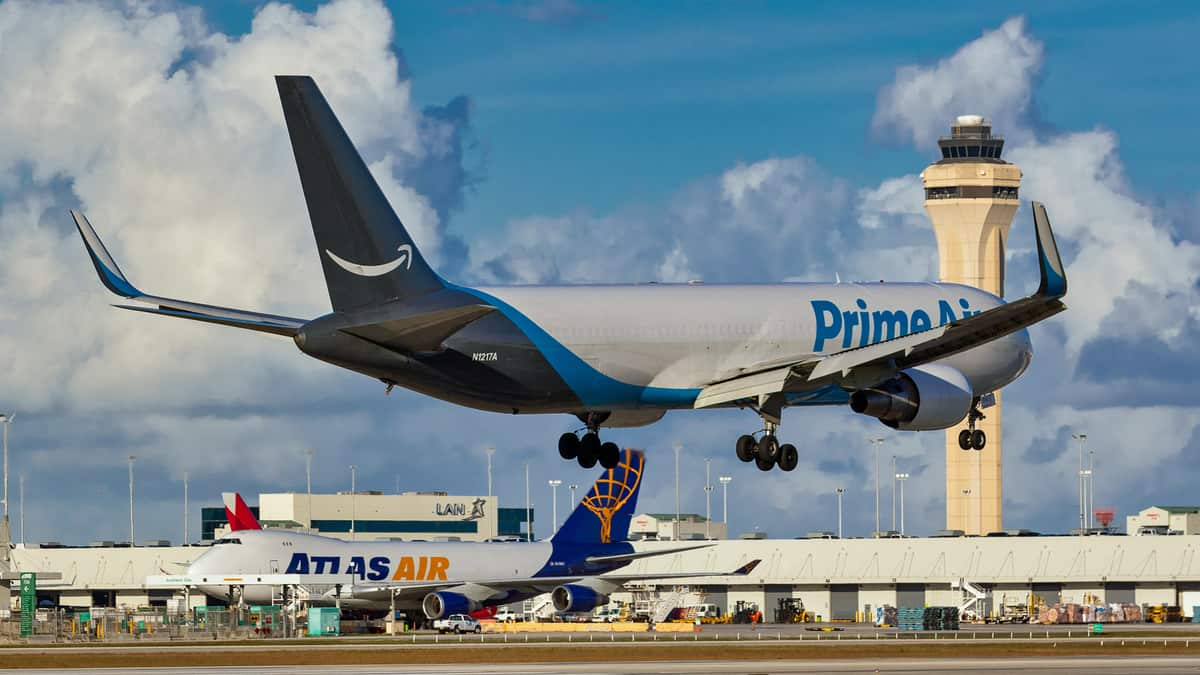 Amazon Prime Air plane comes in for landing at airport.
