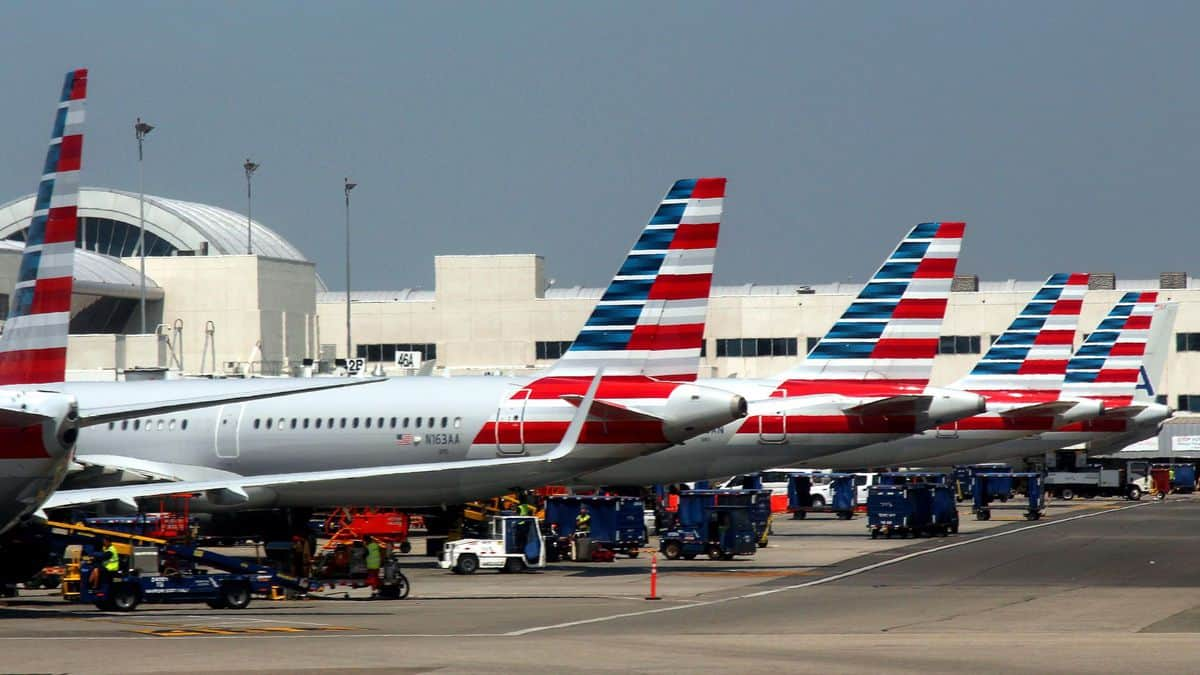 Red, white and blue tails of American Airlines planes at terminal gates.