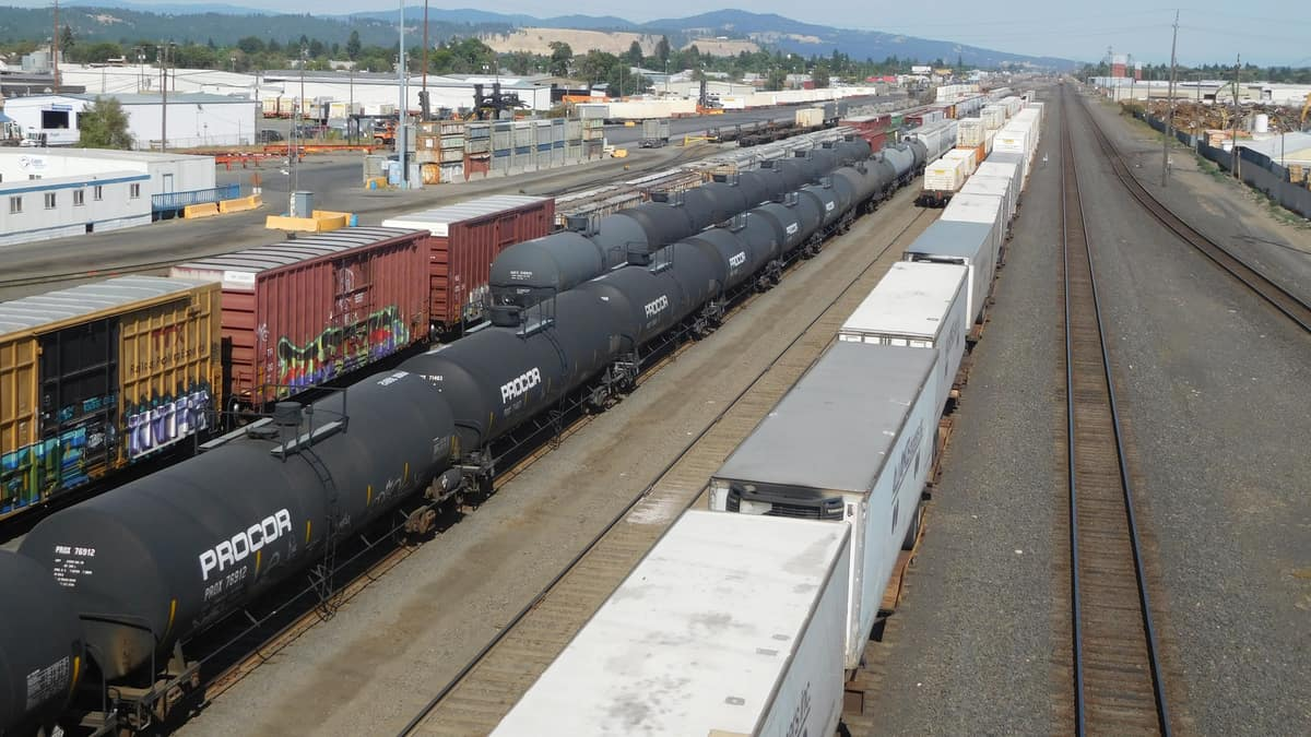 A photograph of a line of boxcars, a line of tank cars and a line of intermodal containers, all parked at a rail yard.
