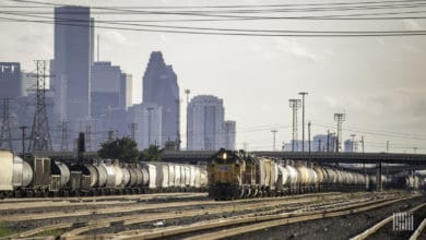 A photograph of a train at a rail yard. There are tall buildings and skyscrapers behind it.
