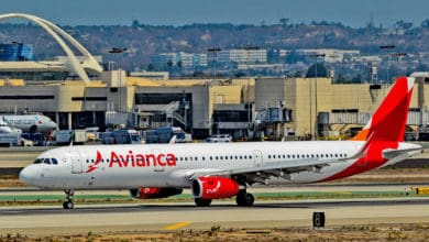 A white and red Avianca plane on the runway.