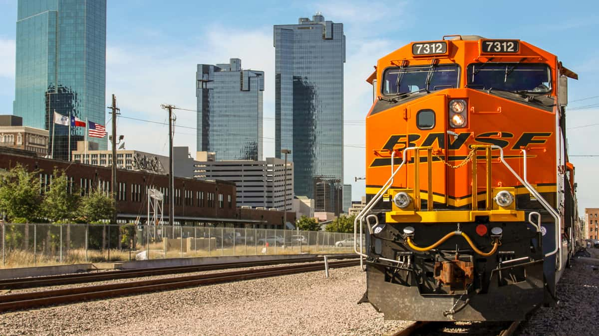 A photograph of a train locomotive on a train track. Behind it are skyscraper buildings.