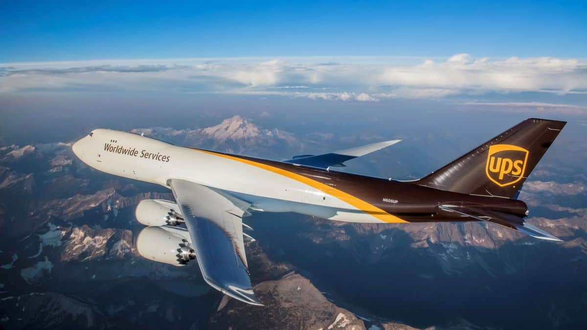 UJPS brown and white jumbo jet flies over mountains.