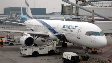 A white El Al plane at the airport gate.